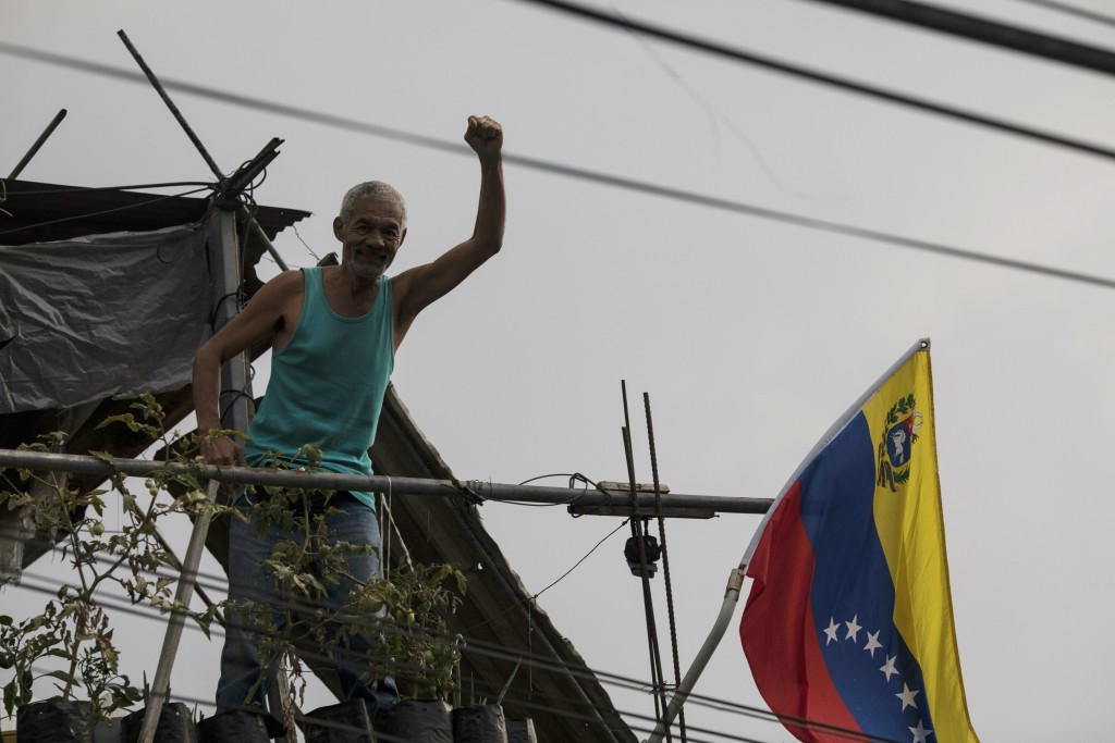 A man holds up his fist to show support for the government of President Nicolas Maduro, from his balcony which overlooks a public square where residen