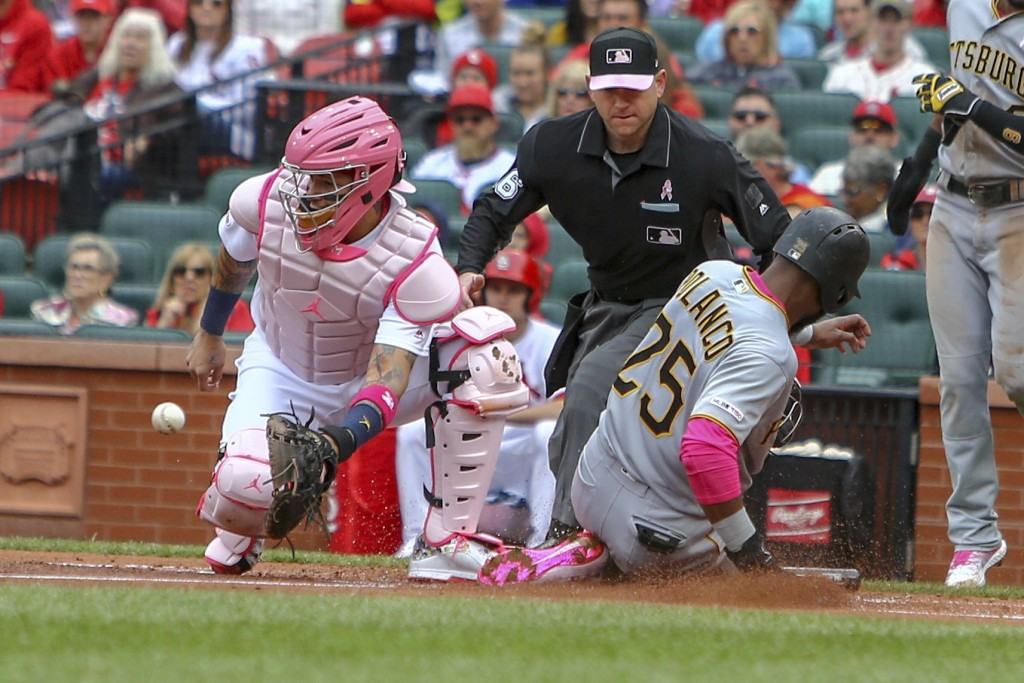 St. Louis Cardinals catcher Yadier Molina, left, waits for the ball as Pittsburgh Pirates' Gregory Polanco (25) slides home to score a run during the