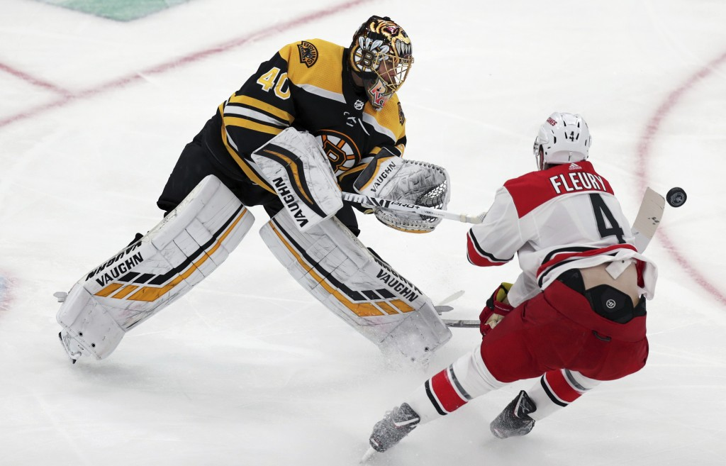 Boston Bruins goaltender Tuukka Rask (40), of Finland, clears the puck as he is pressured by Carolina Hurricanes' Haydn Fleury (4) during the first pe