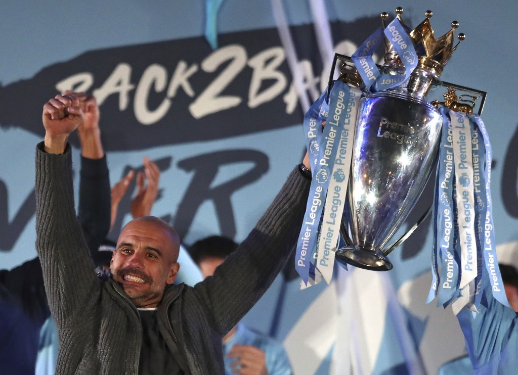 Manchester City coach Pep Guardiola holds the trophy as he celebrates with supporters at the Etihad Stadium in Manchester, England, Sunday May 12, 201