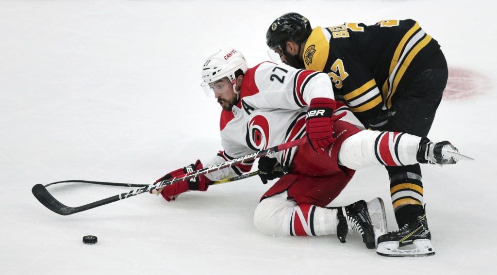 Carolina Hurricanes' Justin Faulk (27) tries to control the puck as he is dropped to the ice by Boston Bruins' Patrice Bergeron, right, during the fir...