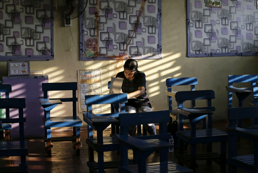 In this Monday, May 13, 2019, file photo, a Filipino woman votes during the country's midterm elections inside a polling center at a school in Manila,