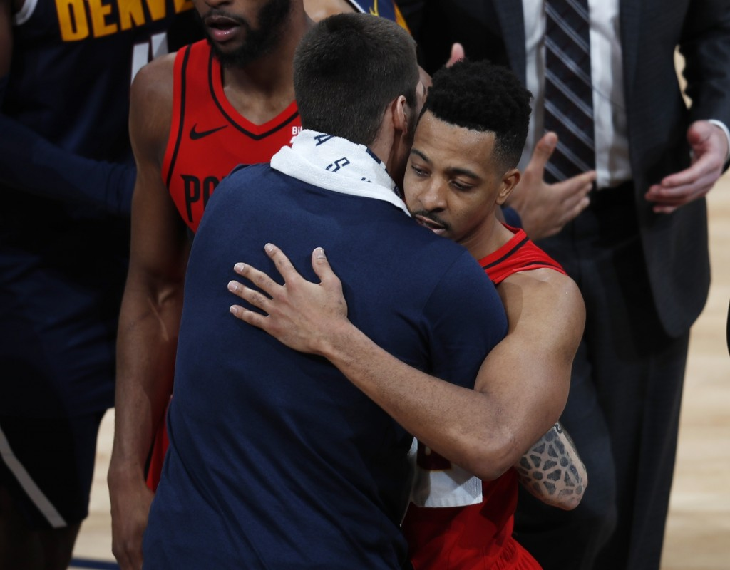 Denver Nuggets forward Juan Hernangomez, left, hugs Portland Trail Blazers guard CJ McCollum after Game 7 of an NBA basketball second-round playoff se
