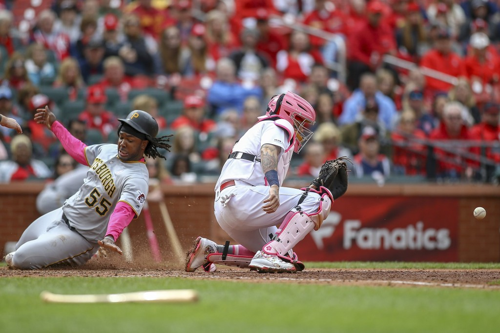 Pittsburgh Pirates' Josh Bell, left, scores a run as St. Louis Cardinals catcher Yadier Molina, right, waits for the ball during the eighth inning of