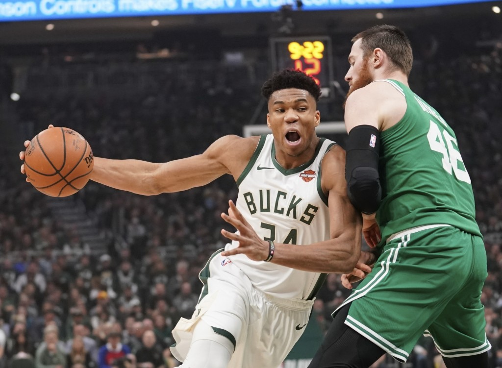 File-This May 8, 2019, file photo shows Milwaukee Bucks' Giannis Antetokounmpo driving past Boston Celtics' Aron Baynes during the first half of Game