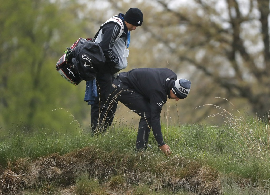 Xander Schauffele, picks his ball out of the rough on the 4th hole during a practice round for the PGA Championship golf tournament, Monday, May 13, 2