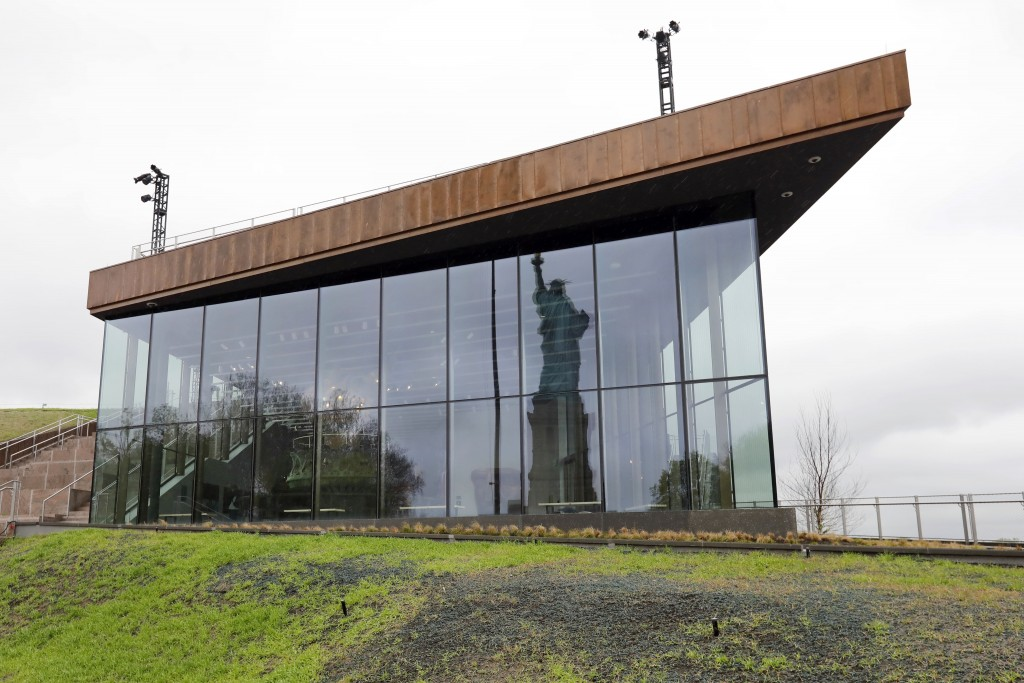 The Statue of Liberty is reflected in the windows of the new Statue of Liberty Museum, on Liberty Island, in New York, Monday, May 13, 2019. (AP Photo
