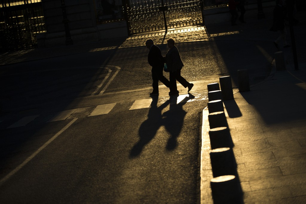 FILE - In this Tuesday, April 4, 2017 file photo, an elderly couple walks across a street near the Royal Palace in Madrid. If you want to save your br...