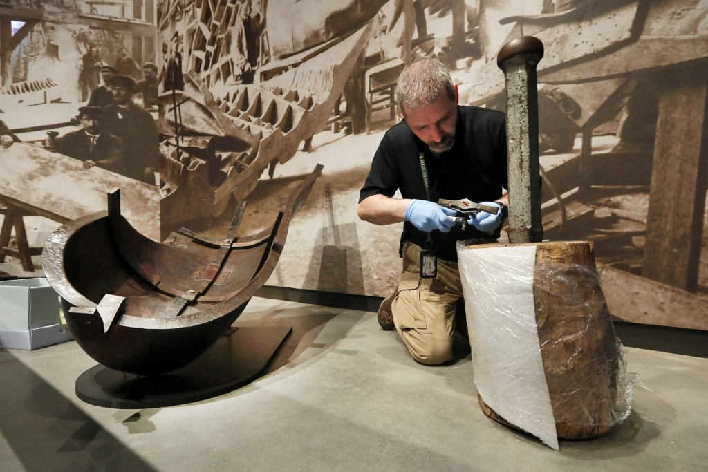 A worker arranges tools in a display of an iron armature in the new Statue of Liberty Museum, on Liberty Island, in New York, Monday, May 13, 2019. (A...