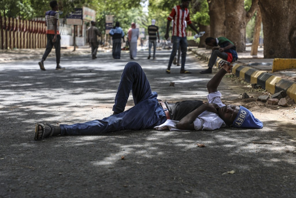A protester takes a rest in a street leading to the sitin outside the Sudanese military headquarters, in Khartoum, Sudan, Tuesday, May 14, 2019. Sudan