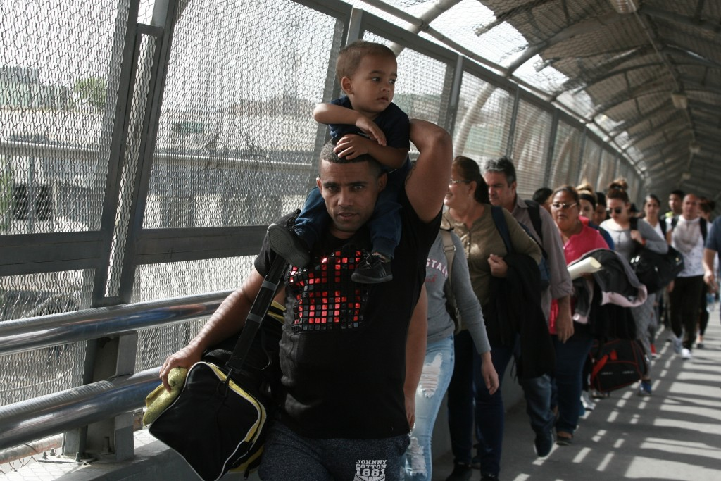 FILE - In this April 29, 2019 file photo, Cuban migrants are escorted by Mexican immigration officials in Ciudad Juarez, Mexico, as they cross the Pas...