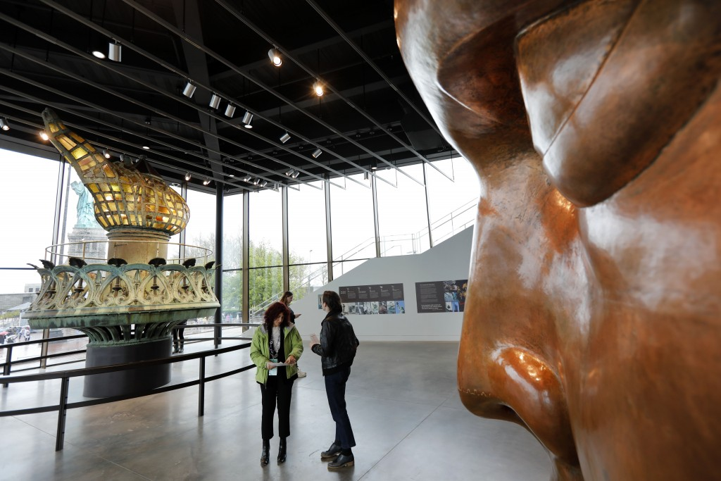 The original torch and flame, and full scale face model, right, are displayed in the new Statue of Liberty Museum, on Liberty Island, in New York, Mon