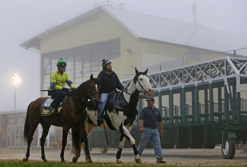 FILE - In this May 15, 2014, file photo, Preakness contender Kid Cruz, left, with exercise rider Reul Munoz aboard, walks past the grandstand after a ...