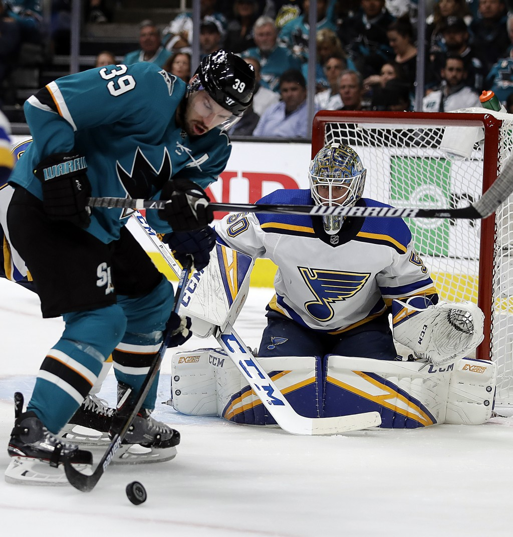 San Jose Sharks' Logan Couture, left, moves the puck against St. Louis Blues goalie Jordan Binnington (50) during the first period in Game 2 of the NH
