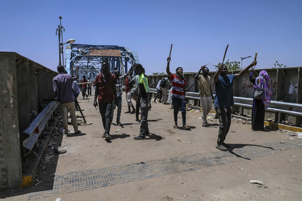 Protesters walk towards the sitin protest outside the Sudanese military headquarters, in Khartoum, Sudan, Tuesday, May 14, 2019. Sudanese protesters s