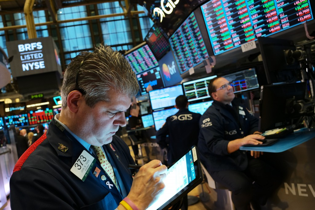 FILE - In this May 13, 2019, file photo John Panin monitors stock prices at the New York Stock Exchange. Corporate profits weren't as bad as analysts