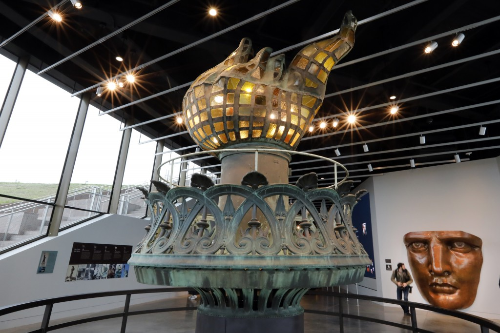 The original torch and flame, and full scale face model are displayed in the new Statue of Liberty Museum, on Liberty Island, in New York, Monday, May