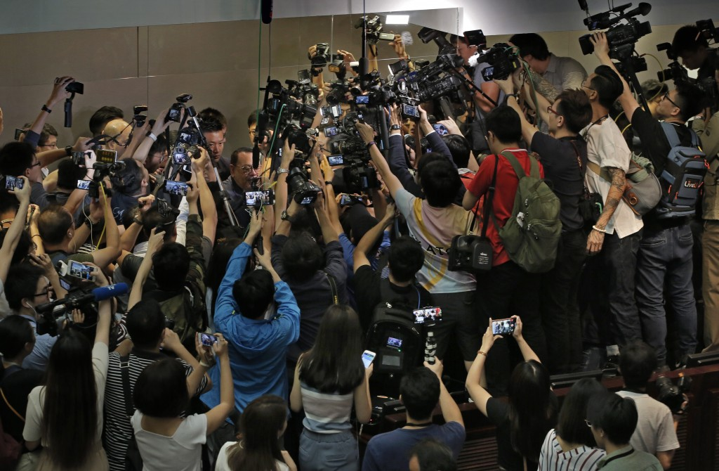 In this Saturday, May 11, 2019, file photo, pro-Beijing lawmaker Shek Lai-him, center with glasses, is surrounded by reporters and photographers durin