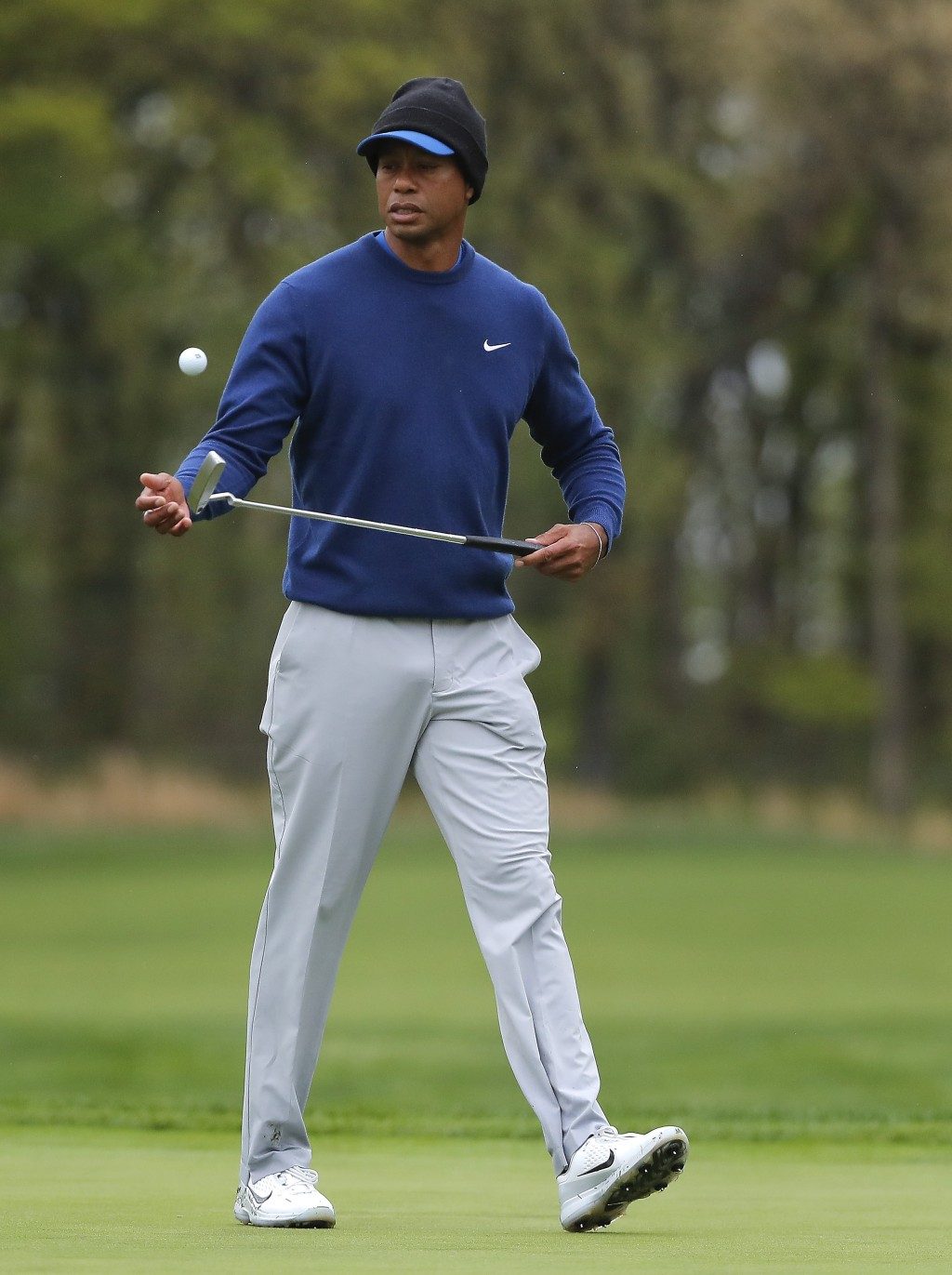 Tiger Woods flips his ball as he walks along the ninth green during a practice round for the PGA Championship golf tournament, Monday, May 13, 2019, i