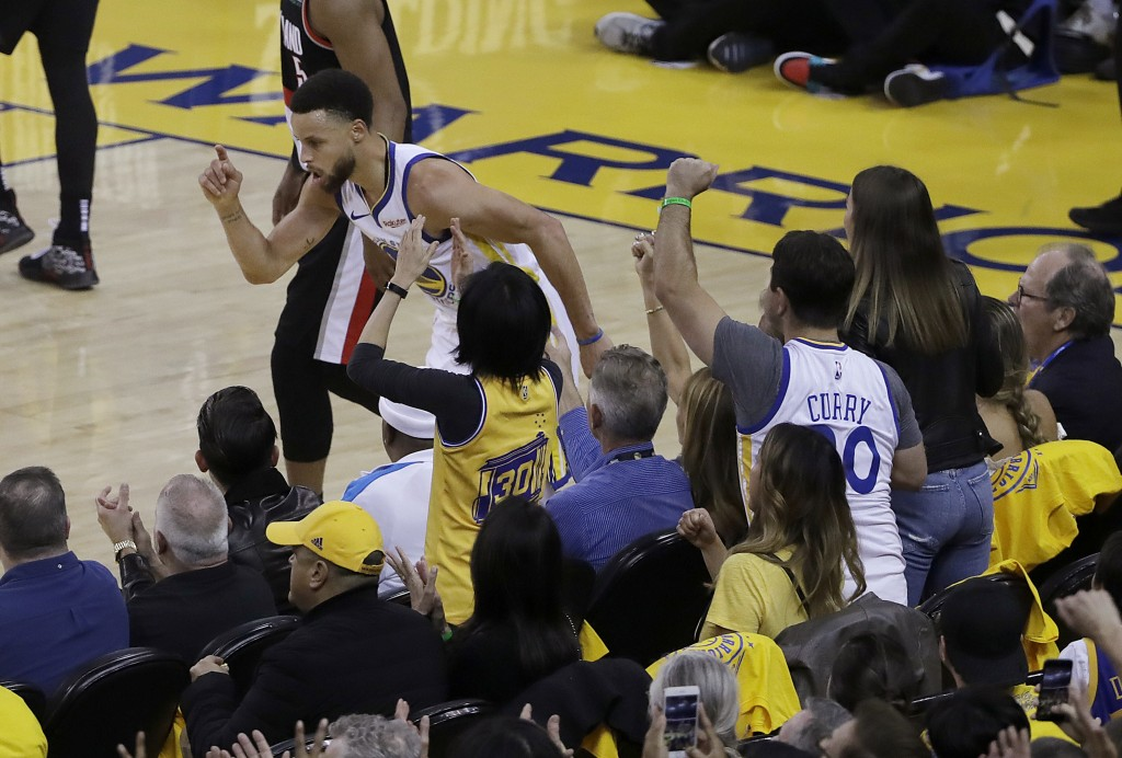 Golden State Warriors guard Stephen Curry celebrates in front of fans after scoring against the Portland Trail Blazers during the first half of Game 1...