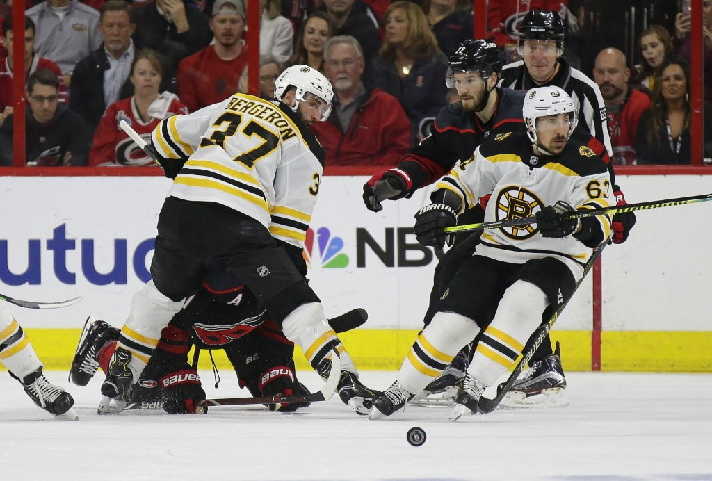 Boston Bruins' Patrice Bergeron (37) and Brad Marchand (63) skate for the puck with Carolina Hurricanes' Brett Pesce (22) and Jordan Staal during the ...