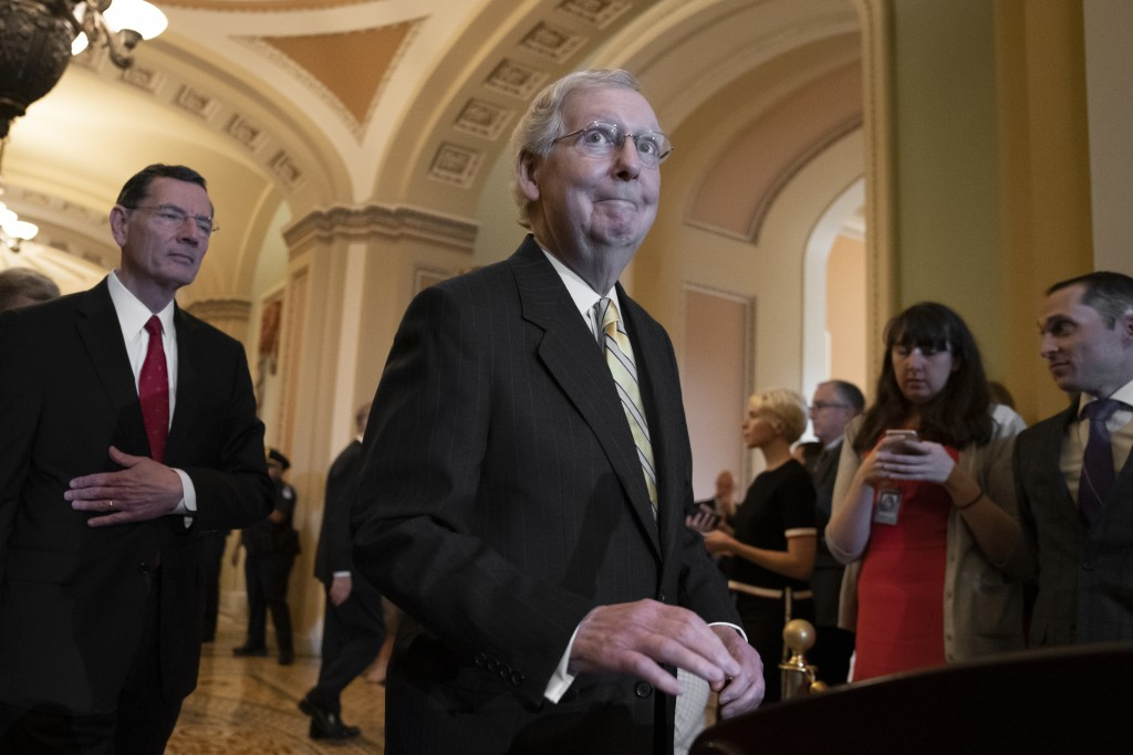 Senate Majority Leader Mitch McConnell, R-Ky., joined at left by Sen. John Barrasso, R-Wyo., answers questions about Senate Intelligence Committee Cha...