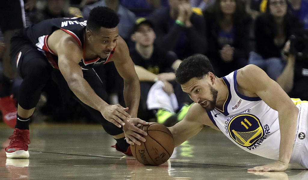 Portland Trail Blazers' CJ McCollum, left, and Golden State Warriors' Klay Thompson reach for the ball during the first half of Game 1 of the NBA bask...