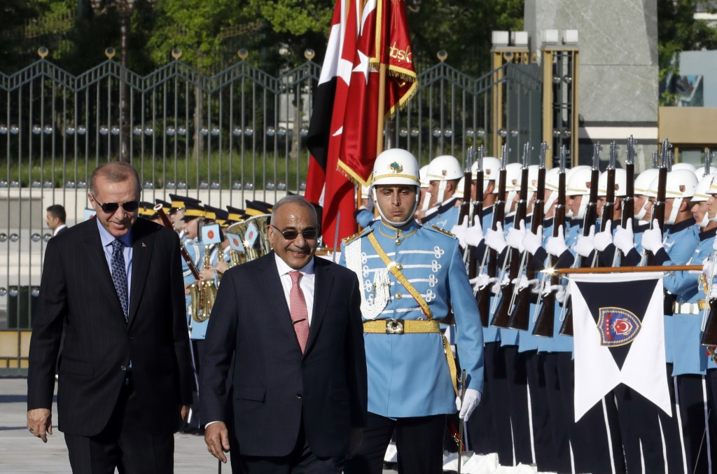 Turkish President Recep Tayyip Erdogan, left, and Iraqi Prime Minister Adel Abdul-Mahdi speak as they inspect an honour guard during a welcome ceremon