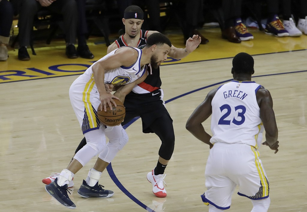 Golden State Warriors guard Stephen Curry, bottom left, is defended by Portland Trail Blazers guard Seth Curry during the first half of Game 1 of the ...
