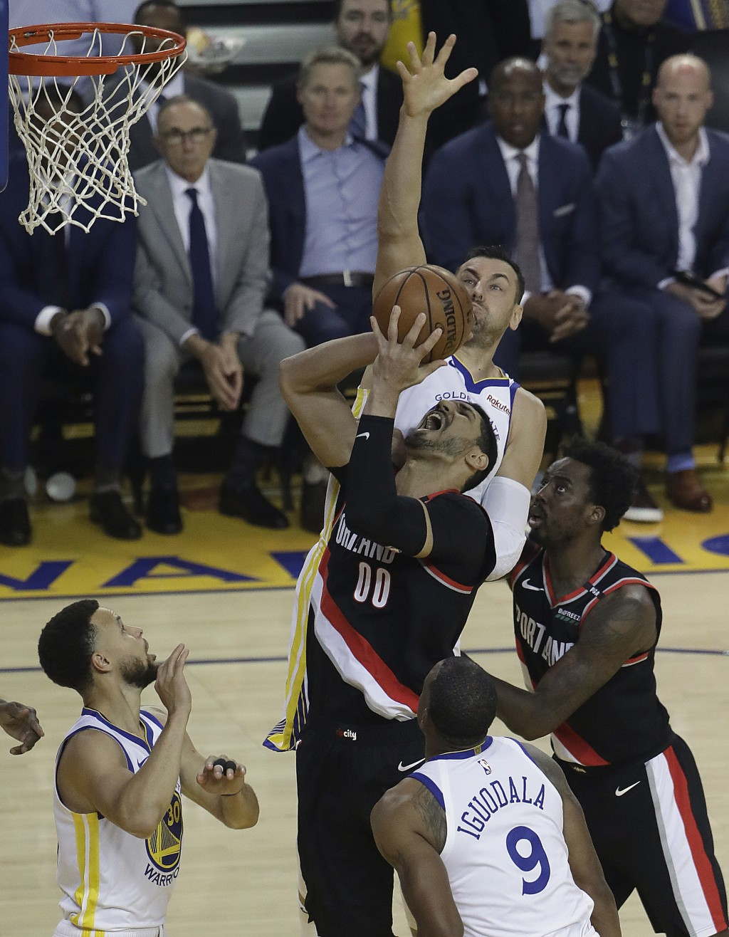 Portland Trail Blazers' Enes Kanter (00) shoots between Golden State Warriors' Andre Iguodala (9) and Stephen Curry, left, during the first half of Ga...