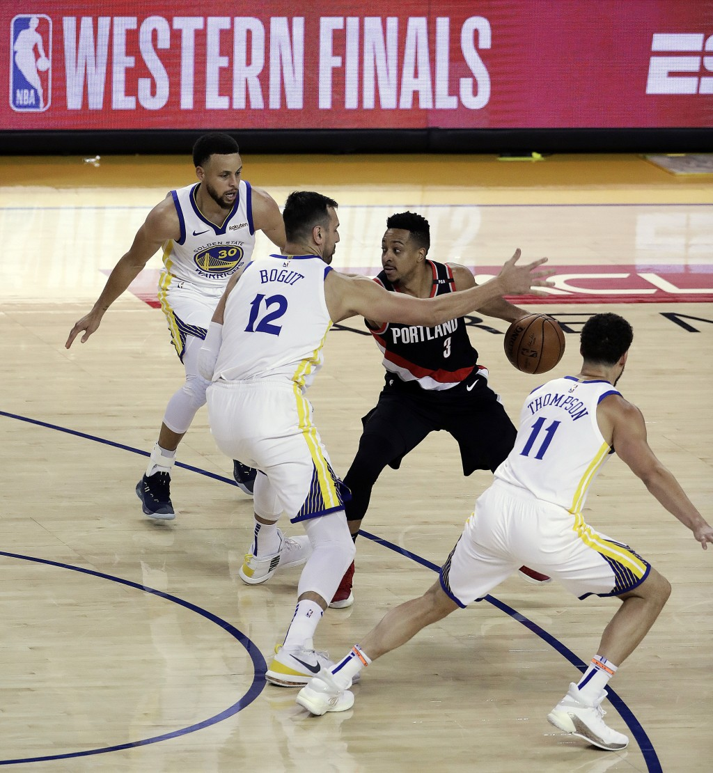 Portland Trail Blazers' CJ McCollum (3) drives the ball against Golden State Warriors' Andrew Bogut (12), Stephen Curry, left, and Klay Thompson (11) ...