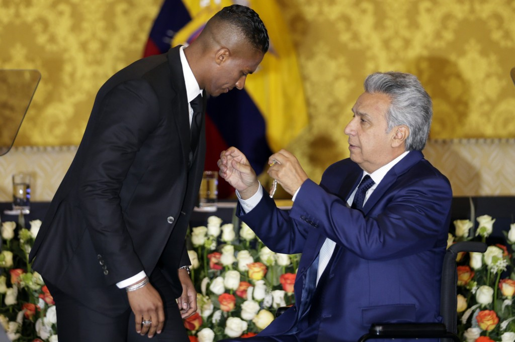 Ecuador's President Lenin Moreno, right, decorates soccer star Antonio Valencia with a National Order of Merit, in Quito, Ecuador, Tuesday, May 14, 20