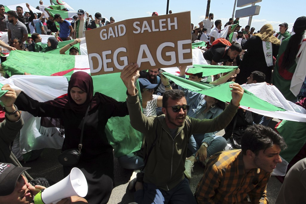 """Algerian students, one carrying a poster reading """"Gaid Salah get out"""" during an anti-government demonstration in Algiers, Tuesday, May 14, 2019. Forme"""
