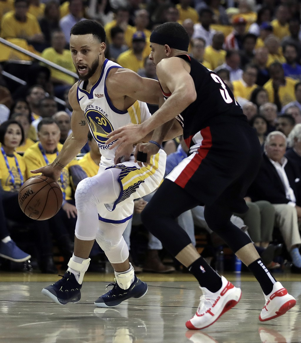 Golden State Warriors' Stephen Curry, left, drives the ball against his brother, Portland Trail Blazers' Seth Curry, during the first half of Game 1 o...