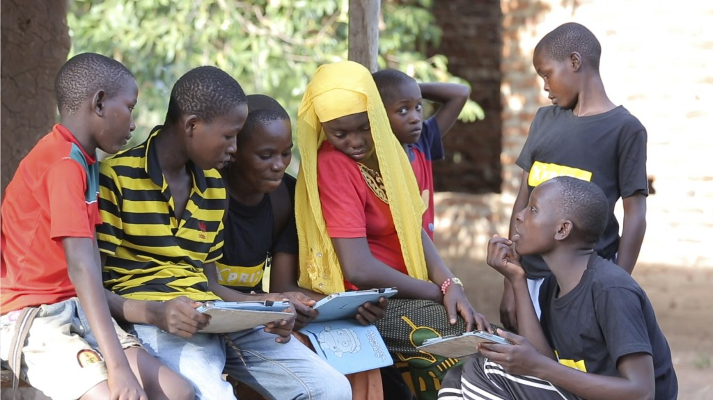 In this undated photo provided by XPRIZE, children in a village in the Tanga region of Tanzania gather to learn from tablets using open-sourced softwa