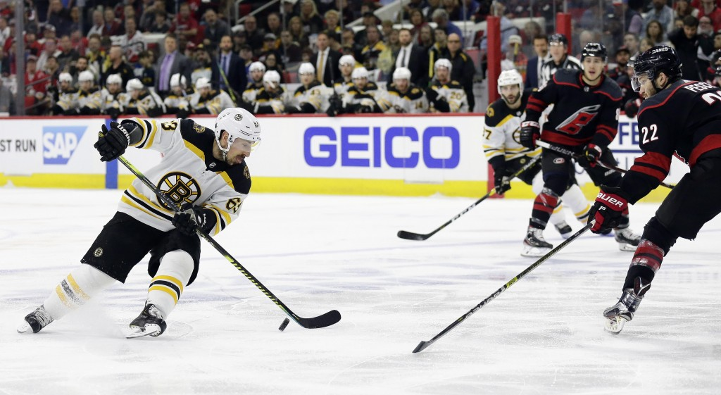Boston Bruins' Brad Marchand (63) controls the puck against Carolina Hurricanes' Brett Pesce (22) during the first period in Game 3 of the NHL hockey ...