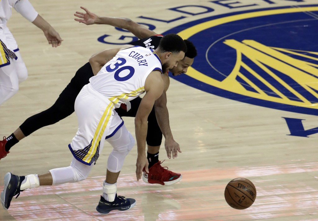 Portland Trail Blazers' CJ McCollum, right, and Golden State Warriors' Stephen Curry (30) chase the ball during the first half of Game 1 of the NBA ba...