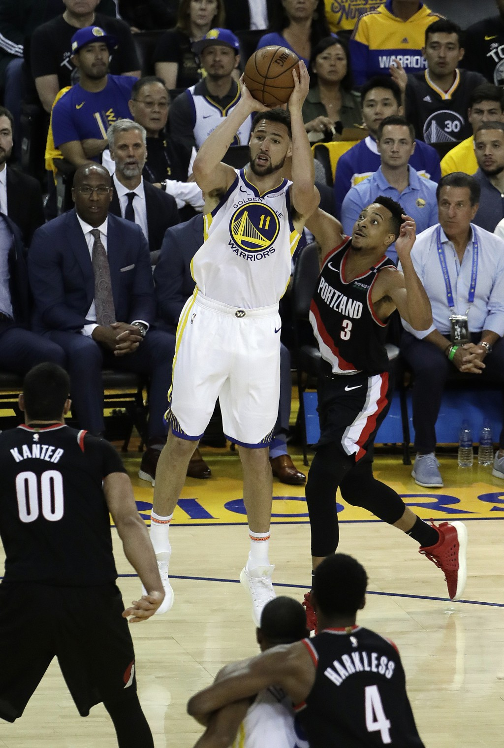 Golden State Warriors' Klay Thompson (11) shoots past Portland Trail Blazers' CJ McCollum (3) during the first quarter of Game 1 of the NBA basketball...