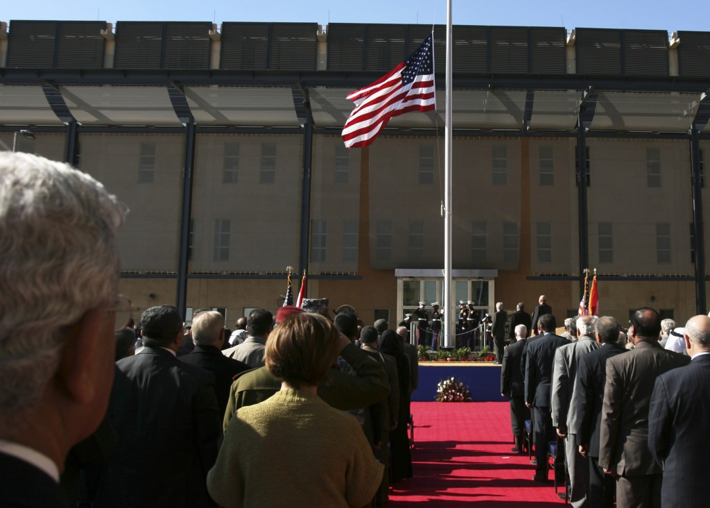 FILE - In this Jan. 5, 2009 file photo, people watch the U.S. flag as it is raised during a ceremony marking the opening of the new U.S. Embassy in Ba