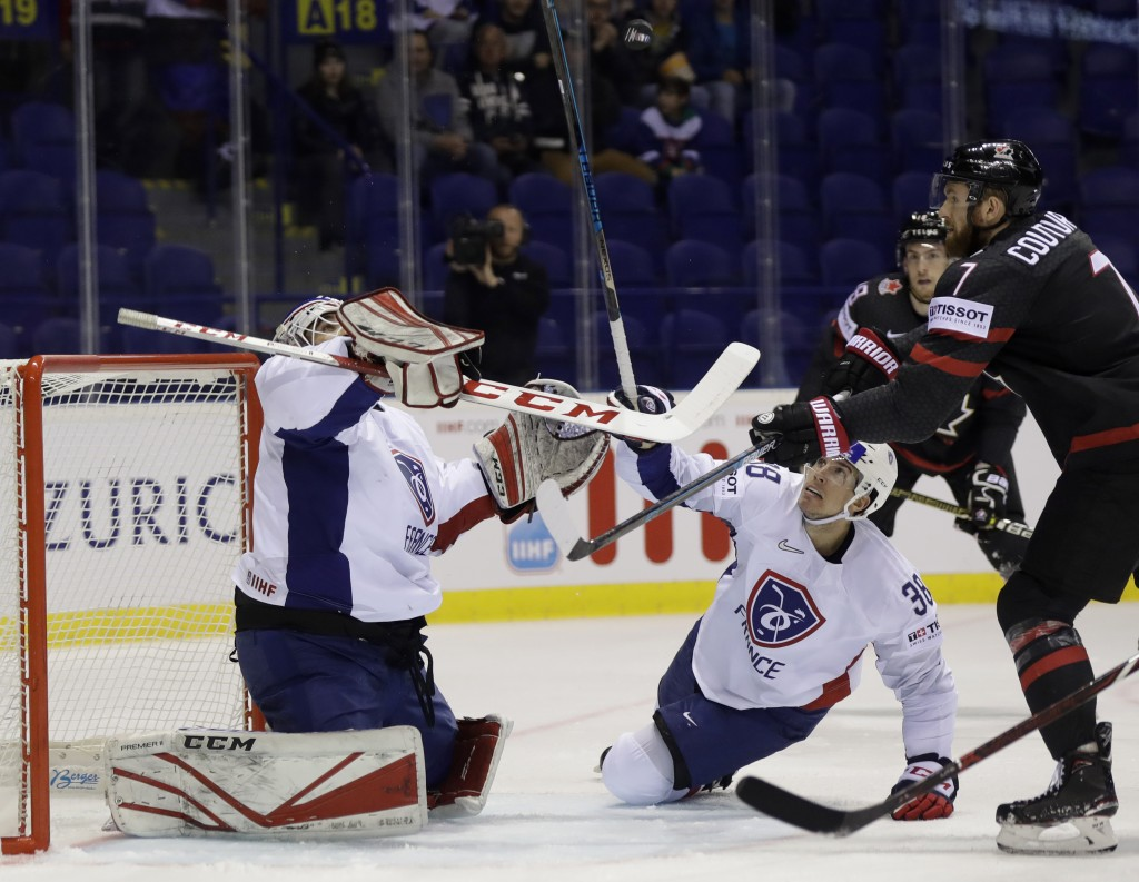 Henri Corentin Buysse of France, left, Pierre Crinon of France, center, challenge Canada's Sean Courtier, right, during the Ice Hockey World Champions