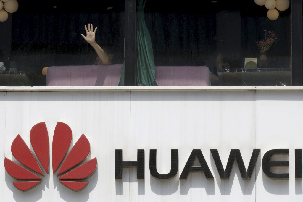 A man presses on the glass window near a logo for Huawei in Beijing on Thursday, May 16, 2019. In a fateful swipe at telecommunications giant Huawei, ...