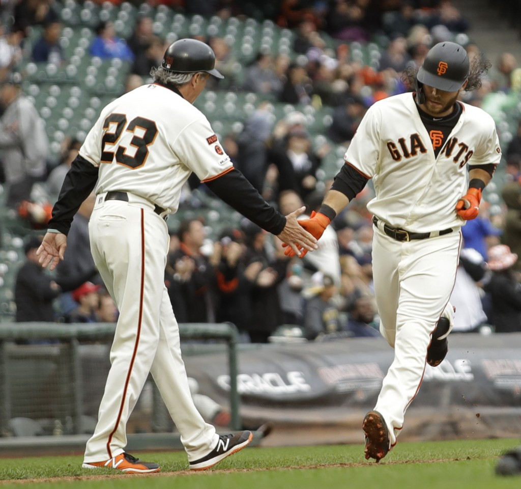 San Francisco Giants' Brandon Crawford, right, is congratulated by third base coach Ron Wotus (23) after hitting a home run in the sixth inning of a b