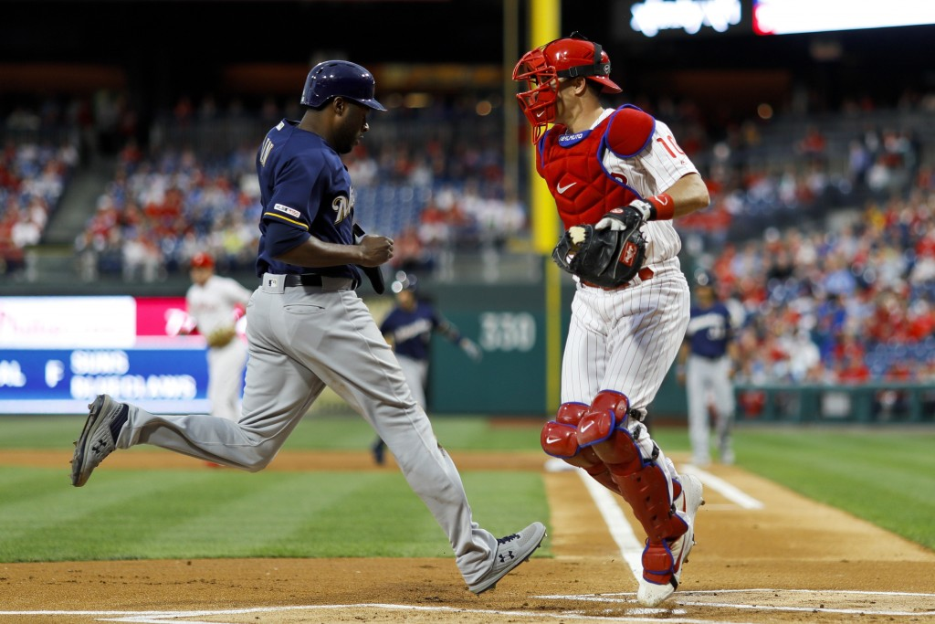 Milwaukee Brewers' Lorenzo Cain, left, scores past Philadelphia Phillies catcher J.T. Realmuto on a single by Ryan Braun during the first inning of a