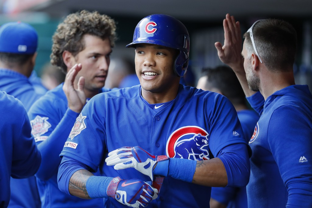 Chicago Cubs' Addison Russell celebrates in the dugout after hitting a two-run home run off Cincinnati Reds starting pitcher Sonny Gray during the sec