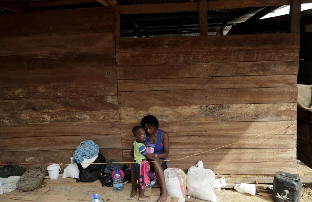 In this May 10, 2019 photo, a migrant woman and her son rest under a wooden house in Peñitas, Darien Province, Panama. According to the National Borde