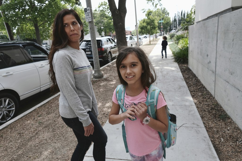 In this Monday May 13, 2019 photo Christina Richner, walks down the street with her children Julian, far right, and Olivia at Horace Mann School in Be