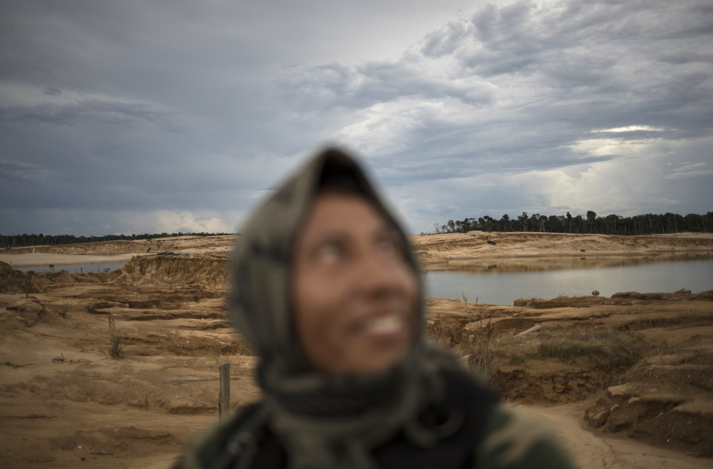 In this April 3, 2019 photo, a police officer smiles while riding in a pick-up truck during a patrol in Peru's Tambopata province. The area known by m...
