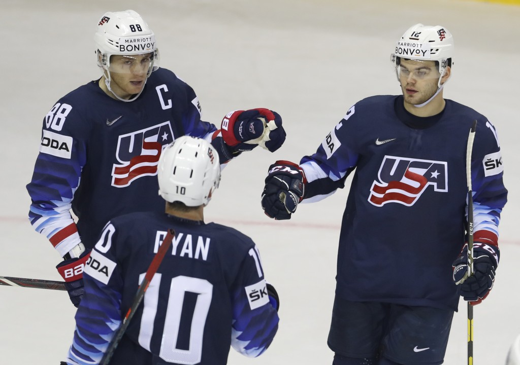 Alex Debrincat of the US, right, celebrates with teammates Patrick Kane, left, and Derek Ryan, center, after scoring his sides fourth goal during the