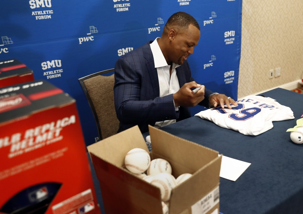 Adrian Beltre, retired MLB baseball player, autographs sports memorabilia before the start of a news conference during the SMU Athletic Forum in Dalla