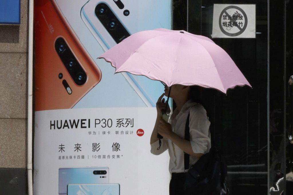 A woman walks past advertisement for Huawei smartphones in Beijing on Thursday, May 16, 2019. In a fateful swipe at telecommunications giant Huawei, t...
